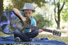 坐在公园和弹吉他的一个小男孩的画象 库存图片