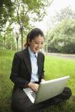 坐在公园和研究她的膝上型计算机的年轻女实业家 库存图片