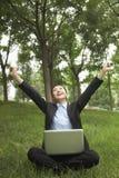 坐在公园和舒展,使用她的膝上型计算机的年轻女实业家 图库摄影
