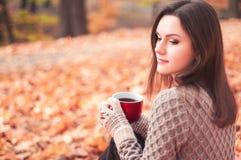 坐在公园和饮用的茶的少妇 库存图片