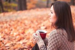 坐在公园和饮用的茶的少妇 免版税库存照片
