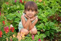 坐在公园夏天的女婴 免版税库存照片