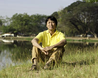 坐在公园的亚裔人 免版税库存照片