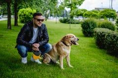 坐在公园的人和狗 免版税库存照片