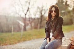 坐在公园的夹克和牛仔裤的美丽的妇女 免版税库存图片