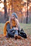 坐在公园的妇女在秋天 免版税库存图片