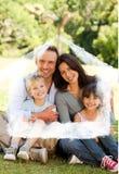 坐在公园的家庭的综合图象 免版税库存图片