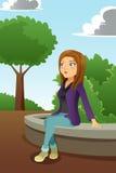 坐在公园的少妇 皇族释放例证