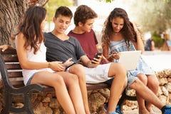 坐在公园的少年朋友使用数字式设备 库存图片