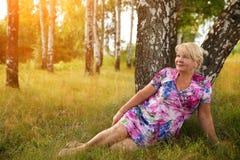 坐在公园的微笑的资深妇女 免版税库存照片