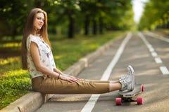 坐在公园的时髦年轻愉快的妇女在longboard和微笑投入了他的脚 溜冰板运动 生活方式 图库摄影