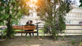 坐在公园的爱恋的夫妇在河附近在秋天 库存照片