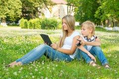 坐在公园的男孩和女孩和享用片剂 库存图片