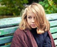 坐在公园的羊毛格子花呢披肩的白肤金发的十几岁的女孩 免版税库存图片