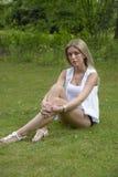 坐在公园的美丽的女孩 图库摄影