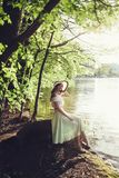 坐在公园的葡萄酒礼服和帽子的美丽的妇女 库存图片