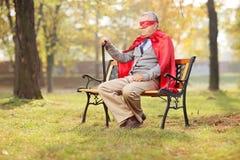 坐在公园的超级英雄成套装备的哀伤的前辈 免版税库存图片