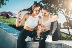 坐在公园的运动服的训练两位女子的运动员,在体育以后放松,用途智能手机,听到音乐 免版税库存照片