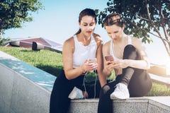 坐在公园的运动服的训练两位女子的运动员,在体育以后放松,用途智能手机,听到音乐 免版税库存图片