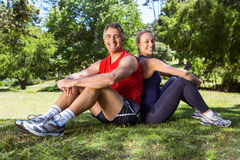 坐在公园的适合的夫妇 免版税库存照片