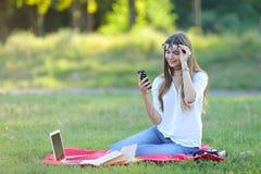 坐在公园,微笑和工作在他的膝上型计算机的女孩,听到音乐 免版税库存照片