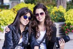 坐在公园,微笑和拥抱的美丽的姐妹 库存照片