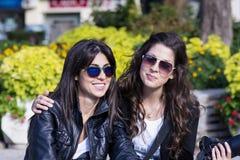 坐在公园,微笑和拥抱的美丽的姐妹 免版税库存照片
