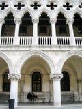 坐在共和国总督的宫殿的曲拱,威尼斯下的妇女 免版税库存照片