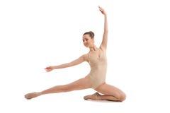 坐在典雅的姿势的年轻俏丽的跳芭蕾舞者 免版税库存图片