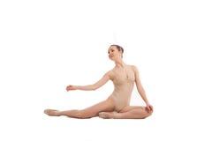 坐在典雅的姿势的年轻俏丽的跳芭蕾舞者 库存图片