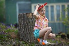 坐在农厂房子附近的困惑的小女孩 自然 免版税库存照片