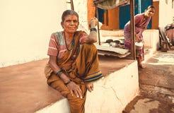 坐在农村家附近的传统礼服的年长妇女在印地安村庄 免版税库存照片