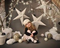 坐在冬天树星场面的孩子 免版税库存照片
