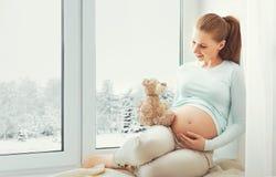 坐在冬天窗口的愉快的孕妇 库存照片