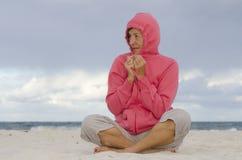 坐在冷秋天天气的海滩的妇女 库存图片