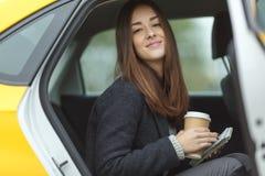 坐在出租汽车的逗人喜爱的女孩 库存照片