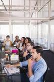 坐在创造性的办公室的周道的企业队 免版税库存图片