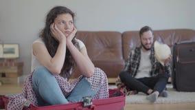 坐在前景的手提箱的生气被触犯的妇女,当她愉快的丈夫包装的材料在旅行前时 股票视频