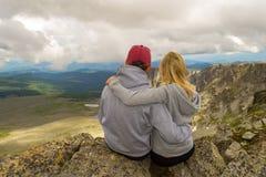坐在前面的岩石容忍边缘的一对爱恋的夫妇 库存照片
