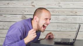 坐在办公室和研究膝上型计算机的微笑的人 股票视频