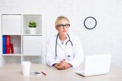 坐在办公室和考虑某事的女性医生画象 免版税图库摄影