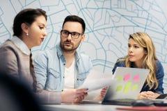 坐在办公室和计划的工作的企业队三 库存照片