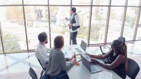 坐在办公室在桌上和使用膝上型计算机,团队工作激发灵感会议概念的年轻雇员 影视素材