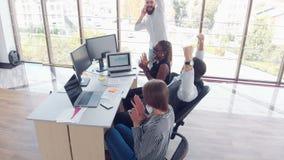 坐在办公室在桌上和使用膝上型计算机,团队工作激发灵感会议概念的年轻雇员 股票录像
