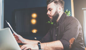 坐在办公室在桌上,读文件和研究膝上型计算机的年轻有胡子的商人 blogging的人,聊天 免版税图库摄影