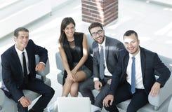 坐在办公室大厅的一个微笑的企业队的画象 免版税图库摄影