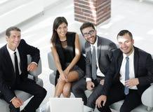 坐在办公室大厅的一个微笑的企业队的画象 库存照片