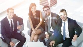 坐在办公室大厅的一个微笑的企业队的画象 免版税库存图片