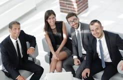 坐在办公室大厅的一个微笑的企业队的画象 图库摄影