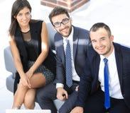 坐在办公室大厅的一个微笑的企业队的画象 库存图片